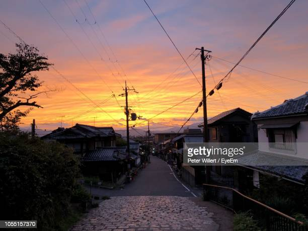 street amidst buildings against sky during sunset - region kinki stock-fotos und bilder