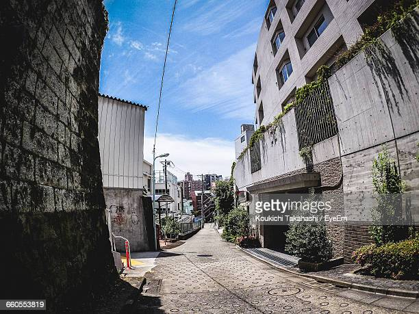 street amidst buildings against sky on sunny day - koukichi koukichi stock photos and pictures