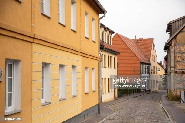 street amidst buildings against sky - east germany stock pictures, royalty-free photos & images