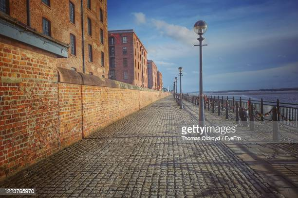 street amidst buildings against sky - diminishing perspective stock pictures, royalty-free photos & images