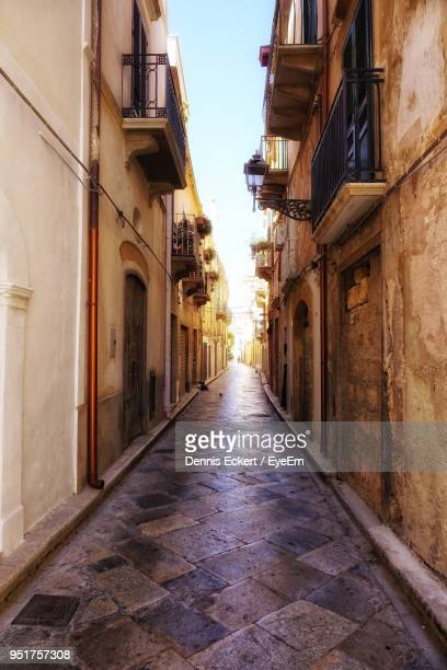 street amidst buildings against sky - narrow stock pictures, royalty-free photos & images