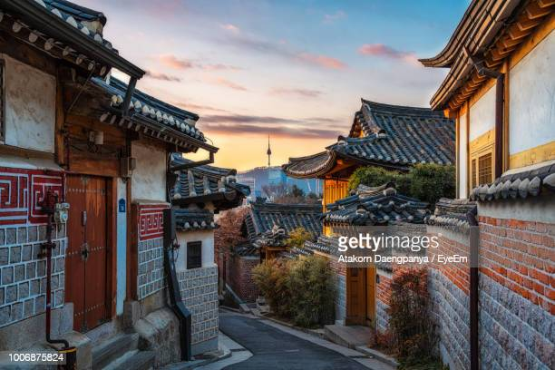 street amidst buildings in city against sky during sunset - seoul stock pictures, royalty-free photos & images