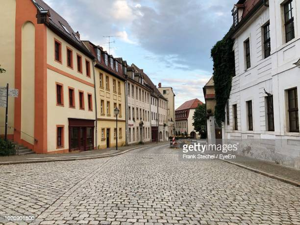 street amidst buildings in city against sky - paving stone stock pictures, royalty-free photos & images