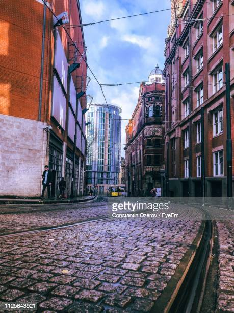 street amidst buildings in city against sky - manchester england stock pictures, royalty-free photos & images