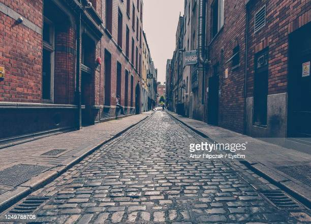 street amidst buildings in city against sky - street stock pictures, royalty-free photos & images