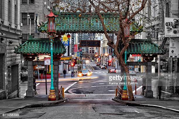 street amidst buildings in city at dusk - chinatown stock pictures, royalty-free photos & images