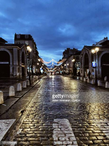 street amidst buildings in city at night - yvelines stock pictures, royalty-free photos & images