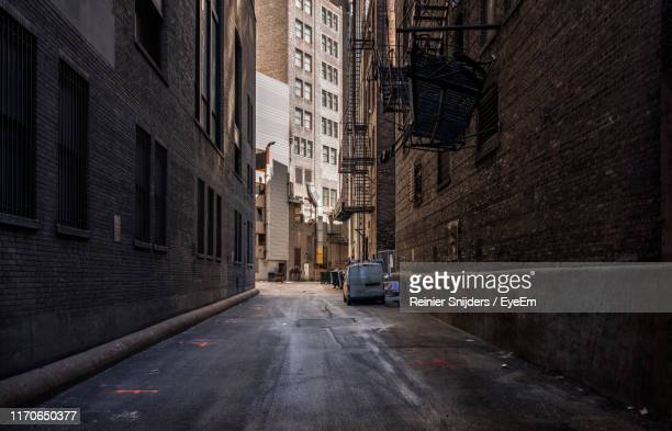 street amidst buildings in city - alley stock pictures, royalty-free photos & images