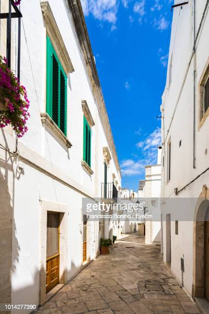 street amidst buildings in town against sky - locorotondo stock photos and pictures
