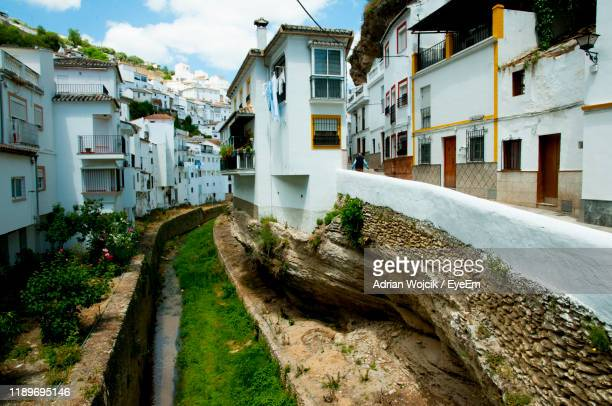 street amidst buildings in town - setenil de las bodegas stock-fotos und bilder