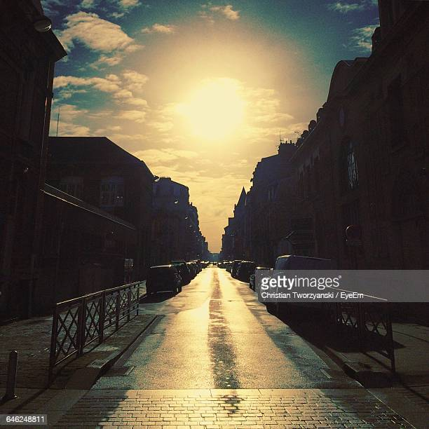 street amidst cars and silhouette buildings at sunset - reims stock pictures, royalty-free photos & images