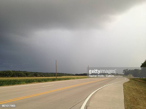 street amidst field against cloudy sky - rachel wolfe stock pictures, royalty-free photos & images