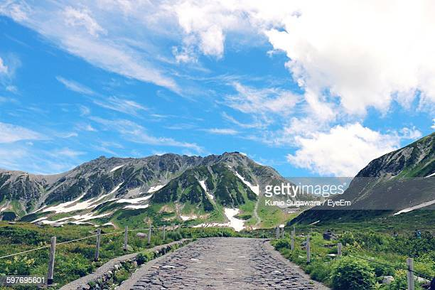 street amidst field by mountains against sky - 富山県 ストックフォトと画像