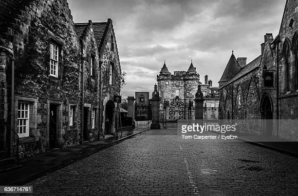 street amidst holyrood palace against cloudy sky - holyrood palace stock pictures, royalty-free photos & images