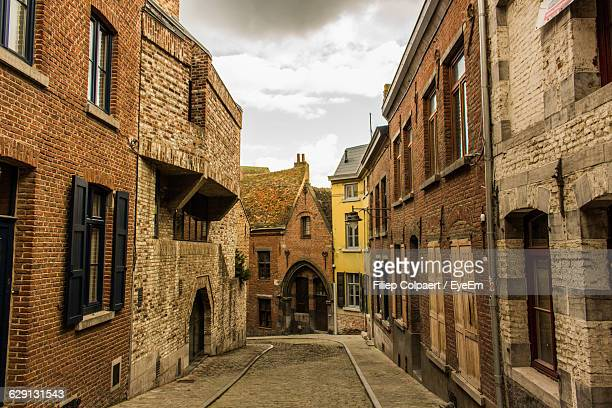 street amidst houses against sky - hainaut stock pictures, royalty-free photos & images