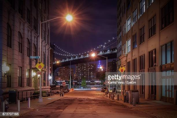 Street Amidst Illuminated Building Against Manhattan Bridge At Night