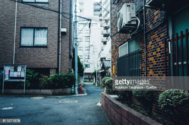 street amidst residential buildings - alley stock pictures, royalty-free photos & images