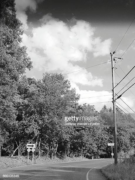 street amidst trees against cloudy sky - wasser stock pictures, royalty-free photos & images