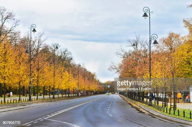 Street Amidst Trees Against Sky During Autumn