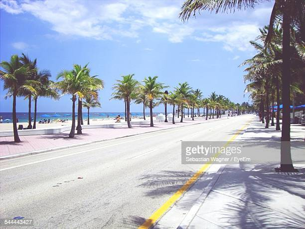 street amidst trees against sky - fort lauderdale stock pictures, royalty-free photos & images