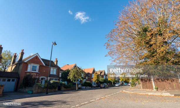 street amidst trees and buildings against blue sky - district stock pictures, royalty-free photos & images