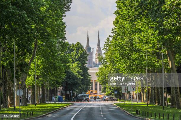street amidst trees and buildings against sky - zagreb stock-fotos und bilder