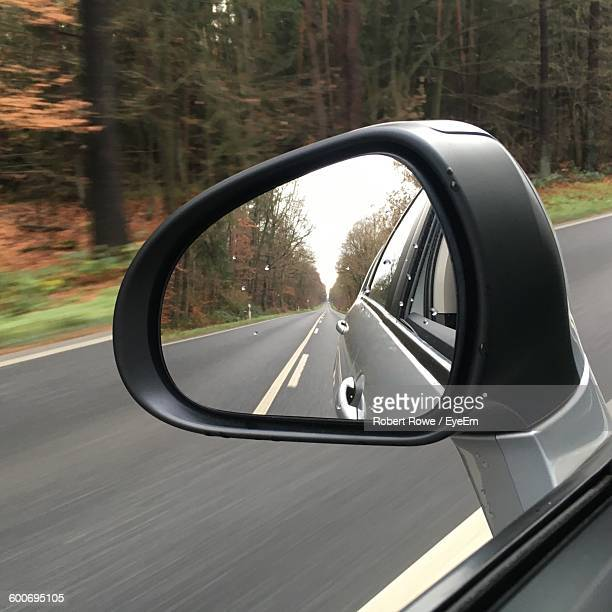 Street Amidst Trees Reflecting On Wet Car Rear-View Mirror