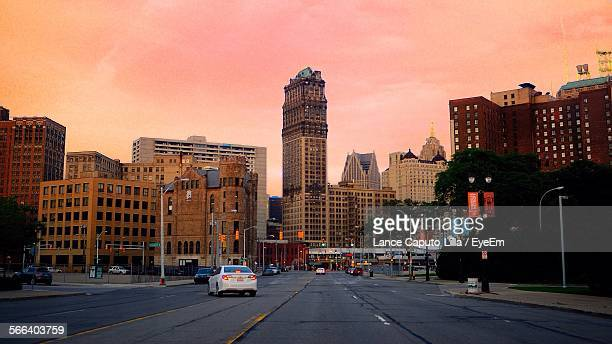 street and cityscape against sky during sunset - デトロイト ストックフォトと画像