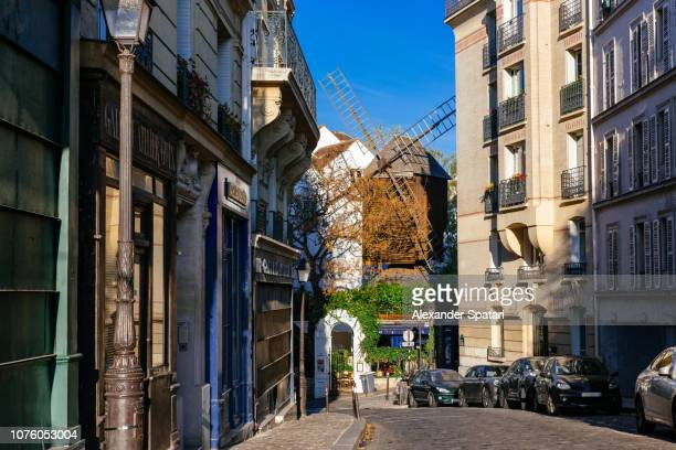 Street and old traditional windmill in Montmartre, Paris, France
