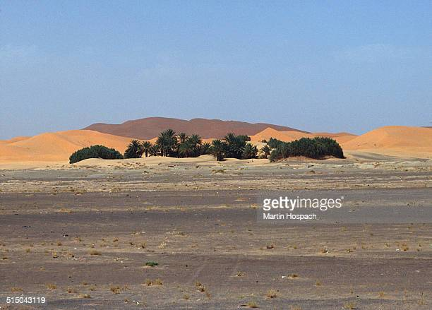 Street and sand mountains in desert against clear sky, Sahara, Al Haouz Province, Morocco