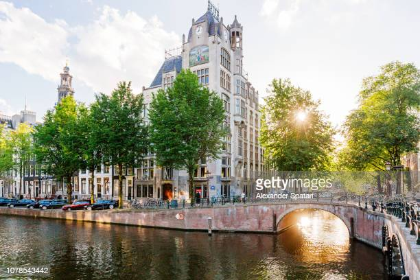 Street and water canal during sunset on sunny summer day, Amsterdam, Netherlands
