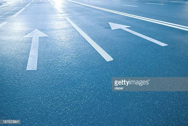 Street arrows pointing into bright light