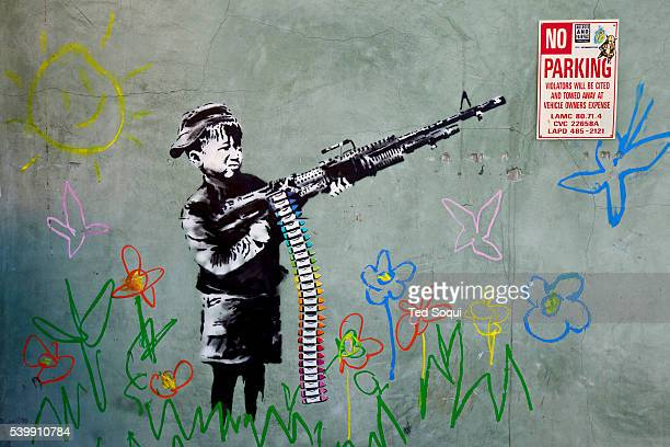 Street art by Banksy in Los Angeles This one is a childlike wall drawing with flowers and a smiley sun with a black and white child holding a machine...