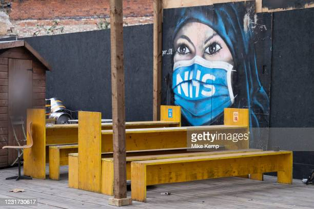 Street art mural of a Muslim woman wearing an NHS face mask in a deserted outdoor bar in Borough as the national coronavirus lockdown three continues...