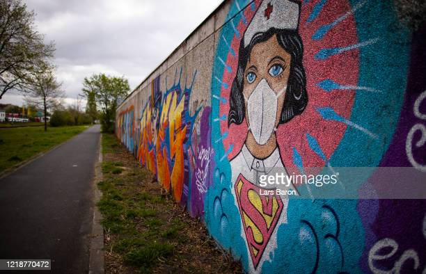 Street art painted by artist Kai 'Uzey' Wohlgemuth featuring a nurse as Superwoman is pictured on a wall on April 14, 2020 in Hamm, Germany. So far,...