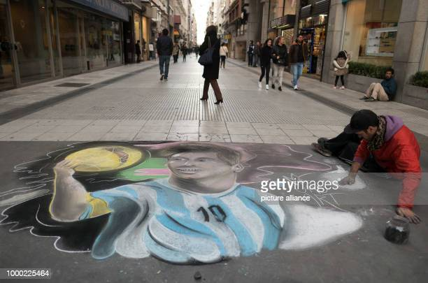 A street artist creates a painting of Argentinian soccer star Lionel Messi in a shopping street in Buenos Aires Argentina 29 June 2017 Messi marries...