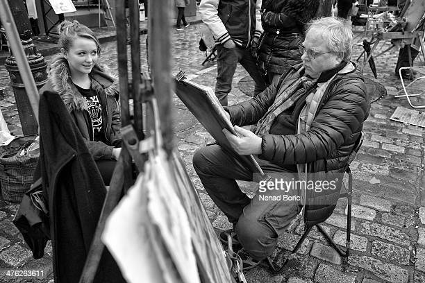 CONTENT] Street artist drawing a portrait of teenage girl on Montmartre square Paris France