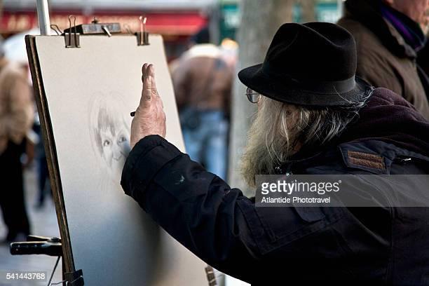 Street artist drawing portrait in Place du Tertre