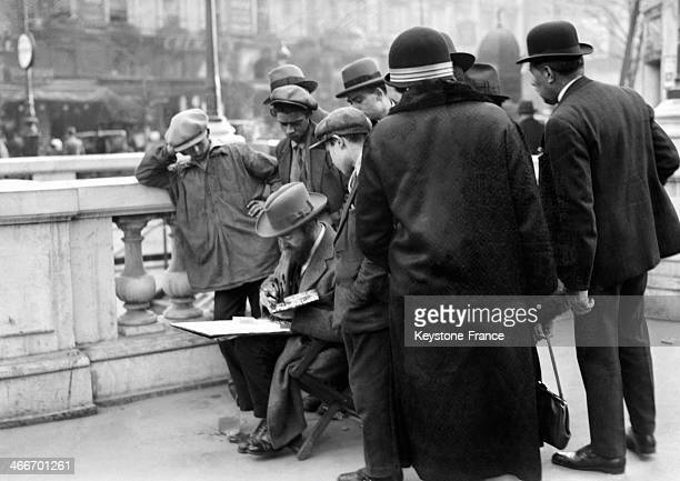 Street artist drawing with people looking in May 1929 in Paris France