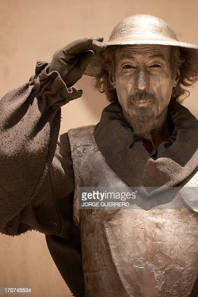 A street artist dressed with a costume of Don Quixote performs in Malaga on June 17 2013 AFP PHOTO/ JORGE GUERRERO