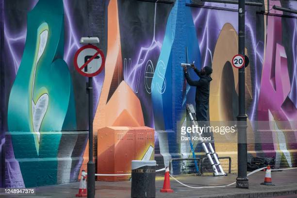 Street artist finishes a large mural that reads ' Black Lives Matter', in Shoreditch on June 11, 2020 in London, England. As the British government...