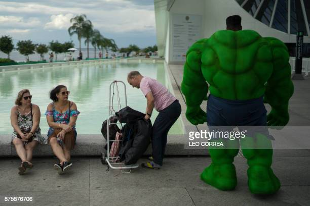 Street artist Henrique Soares in a costume of the comic character Hulk takes a break after performing in Rio de Janeiro Brazil on November 18 2017...