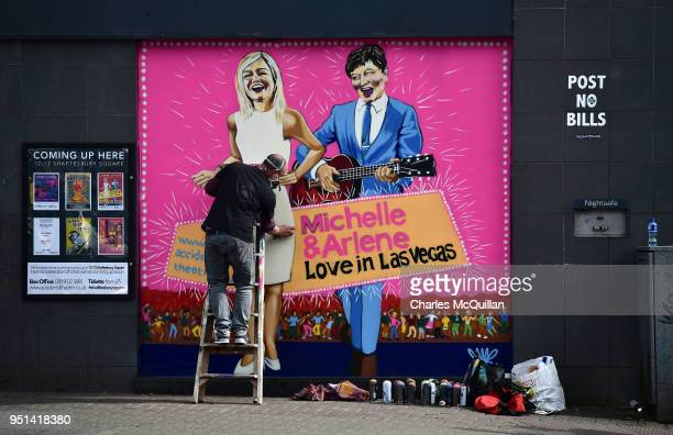 Street artist JMK finishes work on a new mural depicting DUP leader Arlene Foster and Sinn Fein northern leader Michelle O'Neill on April 26 2018 in...