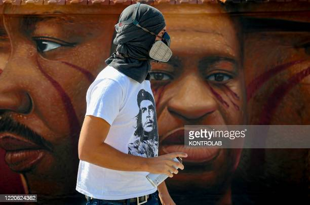 Street artist Jorit Agoch is next to his work, a mural painting on a roof depicting George Floyd, the coloured American killed by a policeman in...