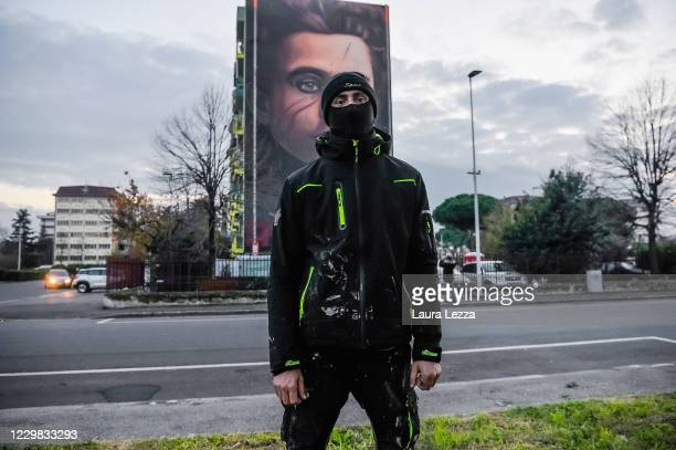 Street artist Jorit poses in front of his mural of philosopher and politician Antonio Gramsci that paid tribute to football player Diego Armando...
