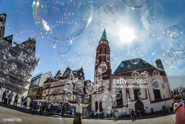 TOPSHOT A street artist makes soap bubbles in front of the Alte Nikolaikirche church at the Roemerberg square in Frankfurt am Main western Germany on...