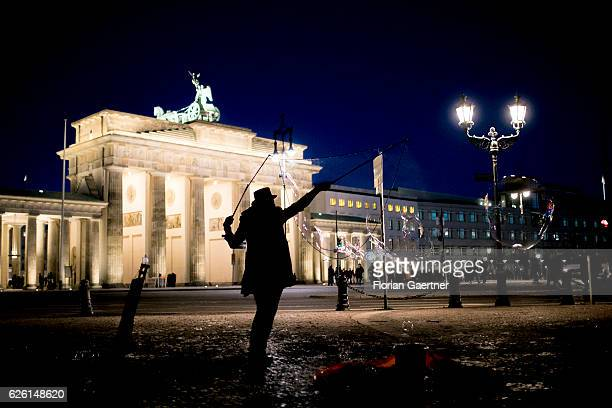 A street artist makes soap bubbles in front of the Brandenburg Gate on November 27 2016 in Berlin Germany
