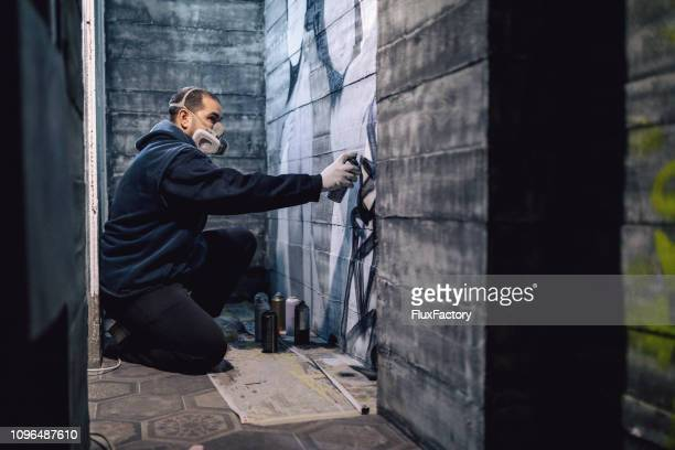 street artist making a spray graffiti on the wall - graffiti foto e immagini stock