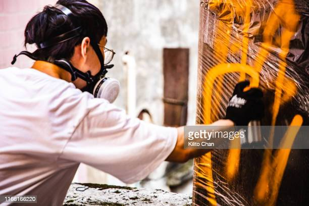 street artist making a spray graffiti on the wall - artist stock pictures, royalty-free photos & images