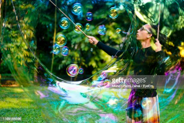 street artist making rainbow bubbles at park - street artist stock pictures, royalty-free photos & images